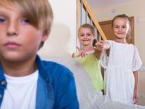 2 говорить девушек и sulky мальчик сидя отдельно дома Стоковые Изображения RF