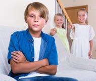 2 говорить девушек и sulky мальчик сидя отдельно дома Стоковая Фотография RF