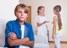 2 говорить девушек и sulky мальчик сидя отдельно дома Стоковые Фото