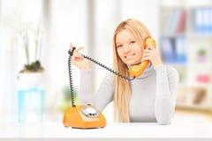 Говорить детенышей усмехаясь женский на телефоне дома стоковые изображения