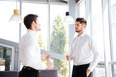 2 говорить и питьевой воды бизнесменов в офисе Стоковая Фотография