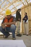 Говорить и работник архитекторов смотря светокопии Стоковое Изображение RF