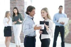 Говорить коллег дела, стоя в современном офисе стоковые изображения rf