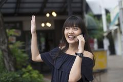 Говорить милой азиатской женщины счастливый на мобильном телефоне и развевать ее рука с ее другом стоковые изображения rf