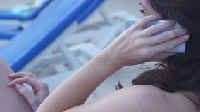 Говорить молодого брюнет женский на smartphone, имеющ переговор сток-видео