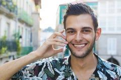 Говорить молодого человека усмехаясь на мобильном телефоне в городе стоковая фотография