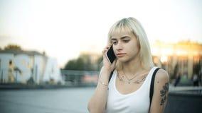 Говорить молодой белокурой женщины сидя на слепимости телефона света захода солнца отразил от стеклянное внешнего акции видеоматериалы