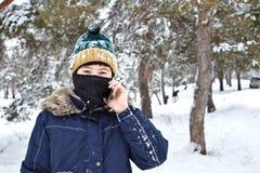 Говорить на мальчике телефона в связанной шляпе с bubo и балаклавой на зиме стоковые фото