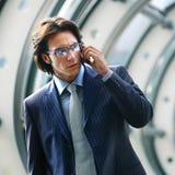 Говорить на мобильном телефоне в лобби офиса Стоковые Фото