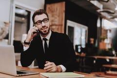 Говорить на телефоне костюм бизнесмена s проект Ноутбук стоковое фото
