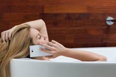 Говорить на телефоне во время ванны Стоковые Изображения