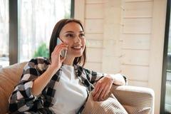 Говорить на телефоне в живущей комнате Стоковая Фотография