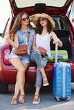 Говорить 2 подруг, сидя в открытом багажнике автомобиля Стоковые Фотографии RF