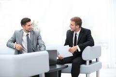 Говорить работников, сидя лобби офиса Стоковое Изображение RF