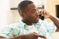 говорить софы телефона человека ослабляя сидя стоковая фотография rf