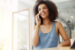 Говорить счастливой жизнерадостной красивой африканской девушки усмехаясь на телефоне сидя в кафе Стоковые Изображения RF