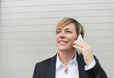 Говорить Smilie исполнительный на телефоне смотря прочь на улице Стоковая Фотография RF