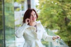 Говорящ на телефоне, зрелая женщина используя клетку стоковая фотография rf