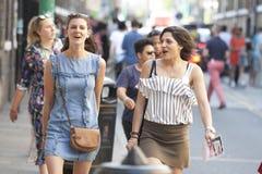 Говоря и смеясь над девушки битника одели в холодном стиле лондонца идя в майну кирпича, улицу популярную среди молодого ультрамо Стоковые Фотографии RF