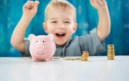 2 года старого ребенка сидя на поле и кладя монетку в piggybank Стоковые Фото