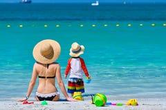 Годовалый малыш 2 играя с матерью на пляже стоковая фотография