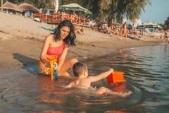 Годовалый мальчик малыша 3 играя с игрушками пляжа с матерью в воде стоковые фотографии rf