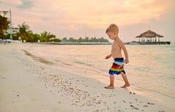 Годовалый мальчик малыша 3 на пляже на заходе солнца стоковое изображение