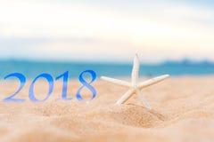 2018 год на песке пляжа с морскими звёздами против голубого неба, счастливый Новый Год 2018 Стоковое Фото