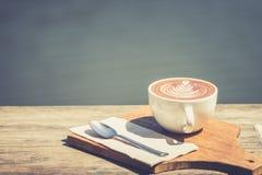 Год сбора винограда горячего искусства капучино кофейной чашки, ложка, ткань, прерывая доска на деревянном столе с космосом экзем Стоковая Фотография