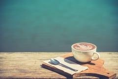 Год сбора винограда горячего искусства капучино кофейной чашки, ложка, ткань, прерывая доска на деревянном столе с космосом экзем Стоковые Фото