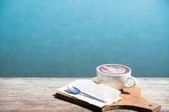 Год сбора винограда горячего искусства капучино кофейной чашки, ложка, ткань, прерывая доска на деревянном столе с космосом экзем Стоковое фото RF