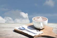 Год сбора винограда горячего искусства капучино кофейной чашки, ложка, ткань, прерывая доска на деревянном столе с космосом экзем Стоковая Фотография RF
