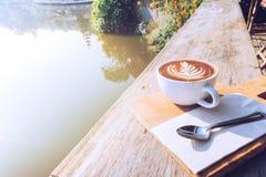 Год сбора винограда горячего искусства капучино кофейной чашки, ложка, ткань, прерывая доска на деревянном столе с космосом экзем Стоковое Фото