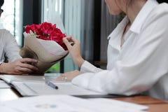 Год сбора винограда тонизировал изображение привлекательной молодой азиатской женщины принимая букет красных роз от парня в офисе Стоковое Фото