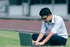 Год сбора винограда тонизировал изображение расслабленного молодого азиатского бизнесмена работая с компьтер-книжкой на зеленой т Стоковые Фото