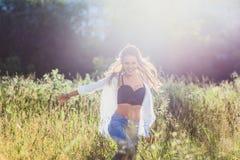 20-год-старая девушка в рубашке и джинсах смеясь над в поле Стоковая Фотография RF