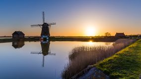 Голландская ветрянка во время захода солнца Стоковое Изображение