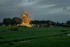 Голландская ветрянка работает и загоренный светами на голубом часе стоковая фотография rf