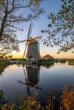 Голландская ветрянка с деревом и отражения в воде на заходе солнца стоковое изображение rf