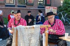 Голландская ярмарка с людьми в традиционной одежде ремонтируя рыболовные сети Стоковые Изображения RF