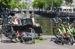 Голландские люди сидя близко к многодельной стоянке автомобилей велосипеда Стоковые Фотографии RF