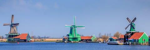 3 голландских ветрянки рядом с рекой против ясного голубого неба Стоковое Изображение RF
