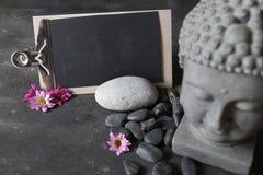 Голова Будды с камнями, цветками и таблитчатым Стоковые Изображения