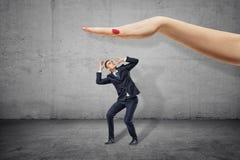 Голова заволакивания маленького бизнесмена с руками и смотреть вверх на руке большой женщины над готовым к тяжелому удару его стоковое фото rf