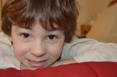 Голова мальчика отдыхая на красном одеяле стоковое изображение