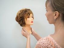 Голова манекена для уча парикмахерских услуг в руках на светлой предпосылке перл макроса имитировать поля детали глубины контейне Стоковое Изображение RF