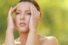 Головка удерживания молодой женщины в боли Стоковое фото RF