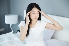 Головная боль женщины на кровати в спальне Стоковые Фотографии RF