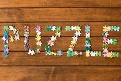 Головоломки надписи от головоломок на деревянном столе против как крюка hang долларов принципиальной схемы приманки предпосылки с стоковые изображения