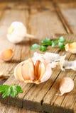 Головы чеснока с петрушкой на деревянном столе Стоковое Изображение RF